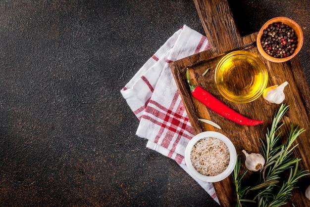 Fondo de cocina, hierbas, sal, especias, aceite de oliva en la tabla de cortar