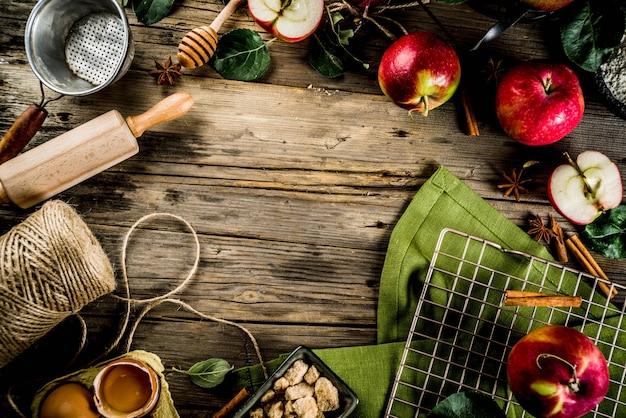 Fondo de cocina de otoño, concepto de horneado de tarta de manzana, manzanas rojas frescas, especias dulces, azúcar, harina, rodillo, huevos, utensilios para hornear, fondo de madera