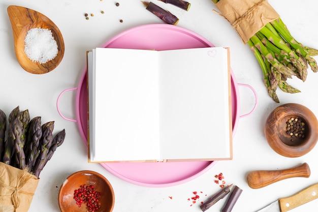 Fondo de cocina con racimos de vegetales de espárragos orgánicos naturales frescos, condimentos y cuaderno para receta.