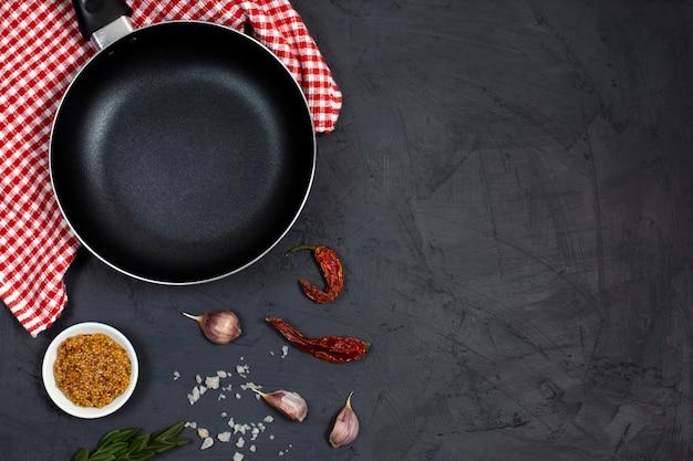 Fondo de cocina con sartén o sartén, especias y hierbas