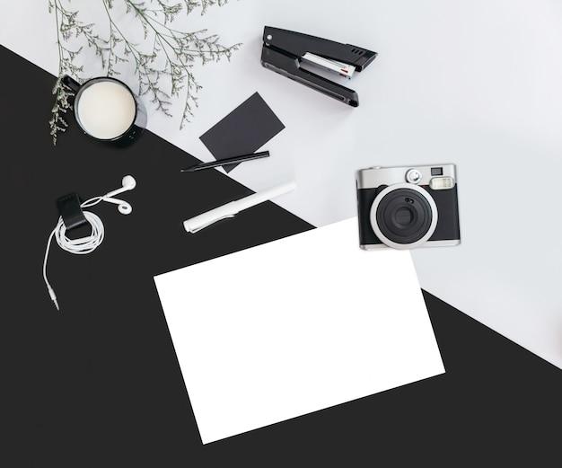 Fondo de color negro y gris con ramas de flores, una taza de leche, auriculares, bolígrafo, grapadora, cámara, tarjeta de presentación y papel blanco. vista superior flay laico