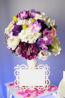 Fondo con coloridas flores en florero y etiqueta vacía para texto