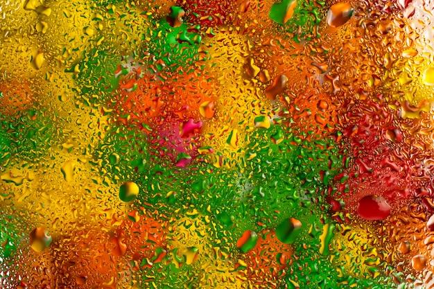 Fondo colorido abstracto de la textura del vidrio con gotas del agua.