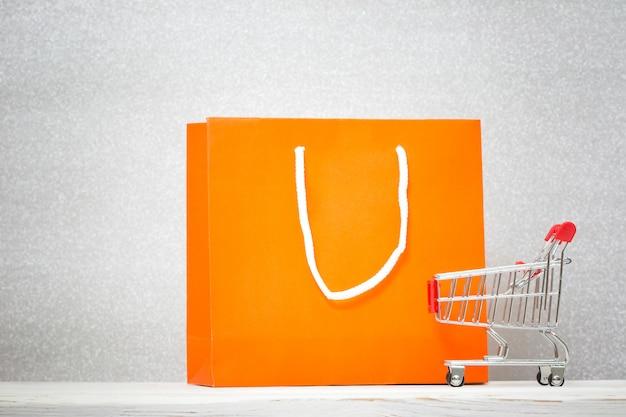 Fondo con colorido bolso de compras y carrito de compras. concepto de descuento
