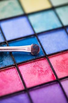 Fondo colorido de la paleta de sombra de ojos con el cepillo del maquillaje