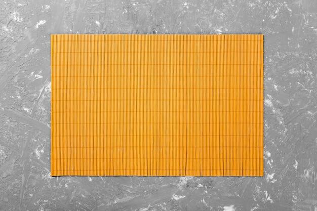 Fondo de comida asiática vacía. estera de bambú amarillo sobre fondo de madera vista superior con copyspace endecha plana