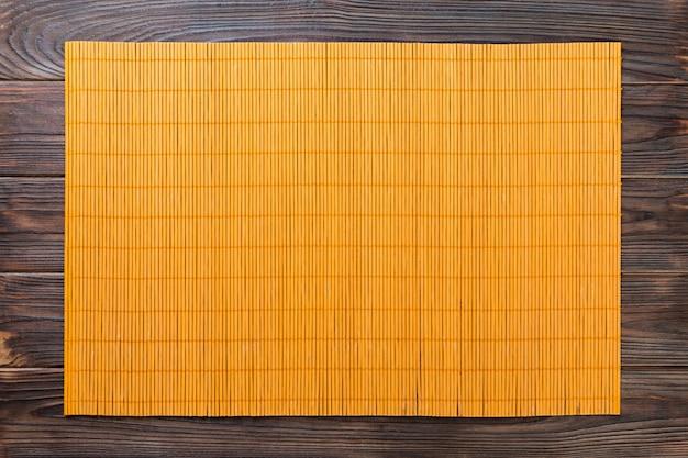 Fondo de comida asiática vacía. estera de bambú amarillo sobre fondo de madera vista superior con espacio de copia plano lay