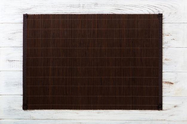 Fondo de comida asiática vacía. estera de bambú oscuro sobre fondo blanco de madera vista superior con copia espacio plano
