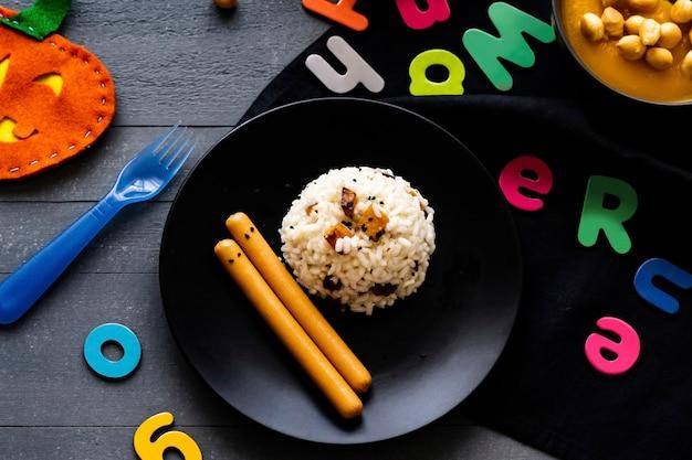 Fondo de comida de fiesta de halloween para niños con risotto de calabaza y salchichas de frankfurt