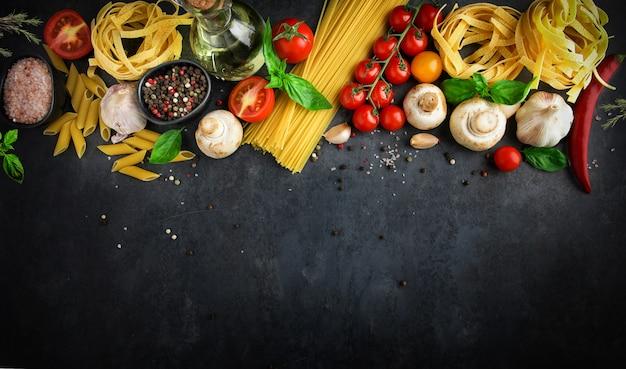 Fondo de comida italiana con ingredientes de pasta sobre fondo oscuro, vista superior, concepto de cocina, restaurante