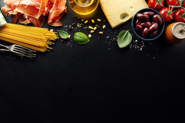 Fondo de comida italiana tradicional con espaguetis tomates queso aceitunas y aceite sobre fondo oscuro.