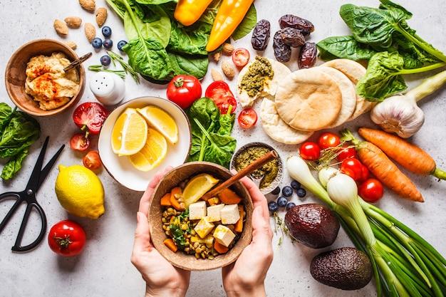 Fondo de comida vegetariana saludable. verduras, pesto y curry de lentejas con tofu.
