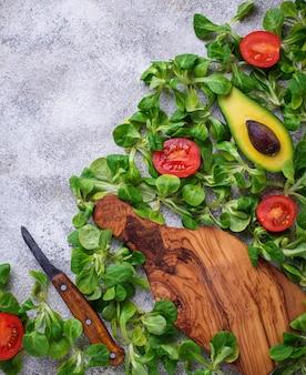 Fondo de comida verde con maíz, lechuga, tomate y aguacate.