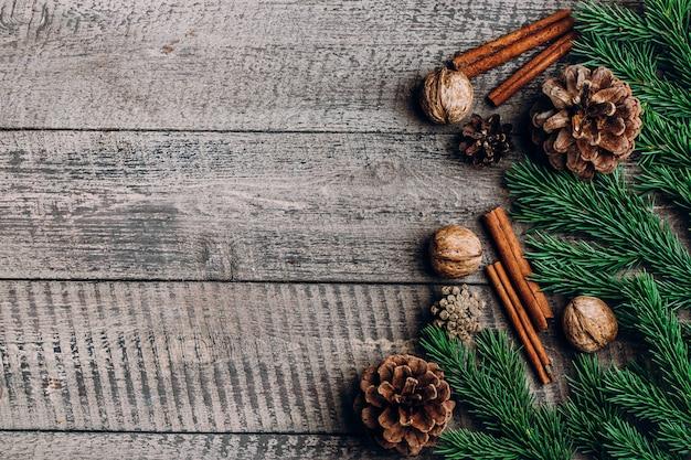 Fondo de composición de navidad. palitos de canela, piñas, ramas de abeto sobre fondo de madera
