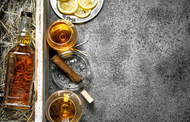 Fondo coñac. una botella de coñac con limón y un puro. sobre un fondo rústico.