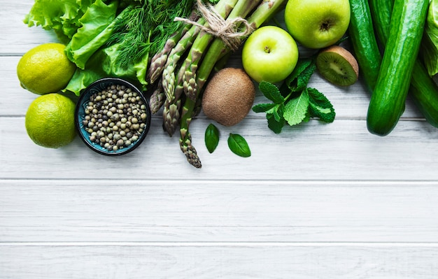 Fondo de concepto de comida vegetariana saludable, selección de alimentos verdes frescos para la dieta de desintoxicación sobre un fondo blanco de madera