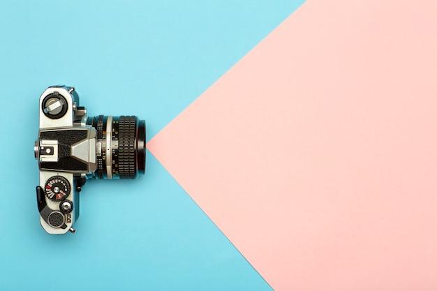 Fondo de concepto creativo de cámara de foto. cámara de fotos retro vintage sobre un fondo coloreado. concepto de viaje, vacaciones y fotografía.