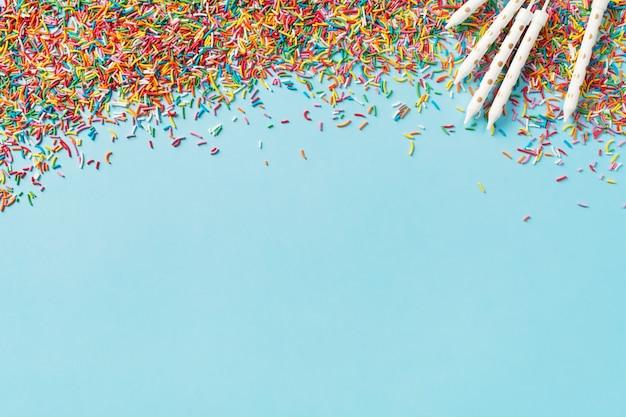 Fondo de concepto de cumpleaños y fiesta con confeti y velas en azul, vista superior, espacio de copia