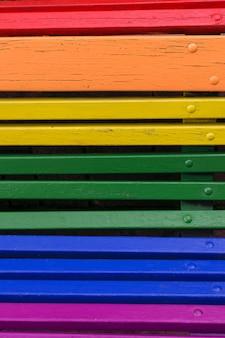Fondo de concepto de día del orgullo. madera de un banco pintado en colores del arco iris.
