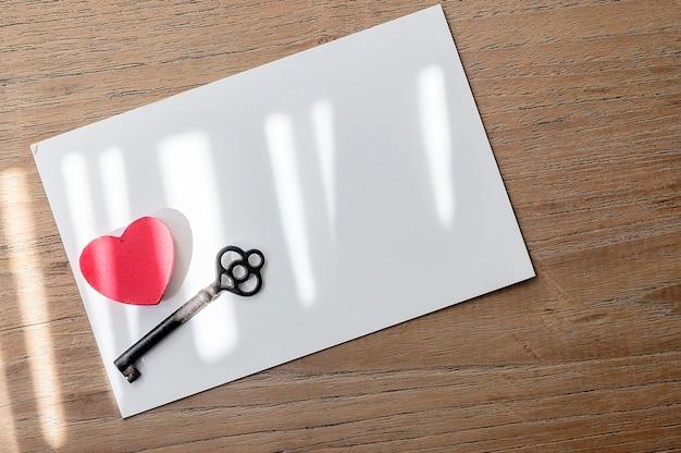 Fondo del concepto del día de san valentín con forma de corazón y vieja llave en la tarjeta de papel blanco.