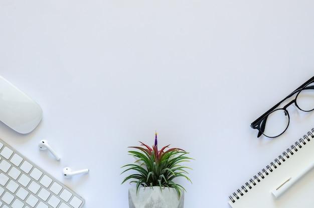 Fondo del concepto de espacio de trabajo con planta de aire tillandsia, ratón, teclado, auricular, cuaderno, bolígrafo y gafas sobre fondo blanco.