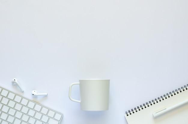 Fondo del concepto de espacio de trabajo con taza de café y material de oficina sobre fondo blanco.