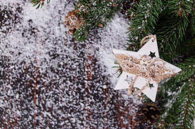 Fondo de concepto de navidad, decoración de estrellas hechas a mano y verdes árboles de navidad en una mesa de madera, salpicada de nieve blanca