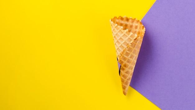 Fondo contrastado con cono de helado vacío.