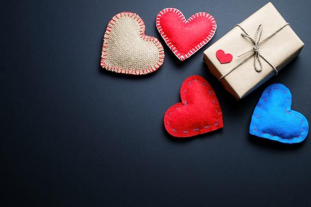 Fondo de corazones rojos y azules o san valentín, sobre un fondo negro. un regalo para la fiesta del día de san valentín, hecho a mano.
