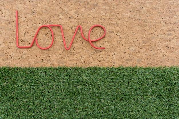 Fondo de corcho con palabra amor y césped