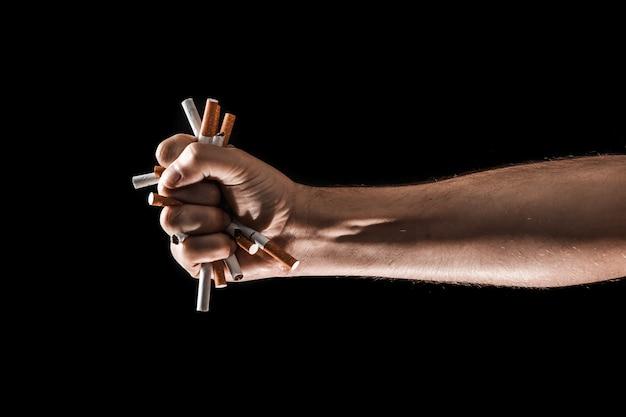 Fondo creativo, mano masculina aprieta el puño de un cigarrillo.