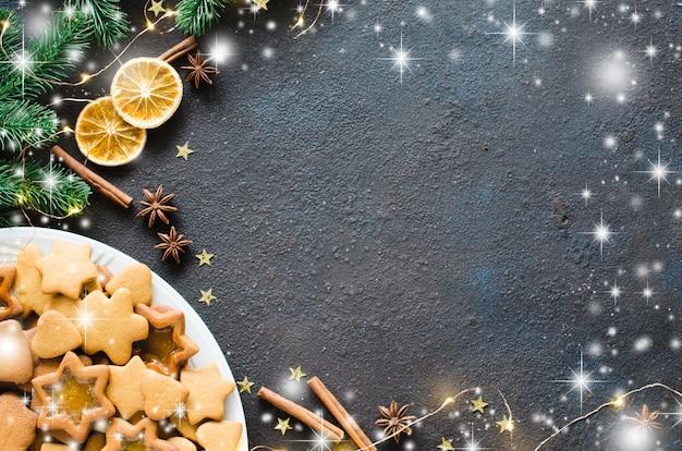 Fondo culinario con pan de jengibre de navidad recién horneado, especias y ramas de abeto. copia espacio