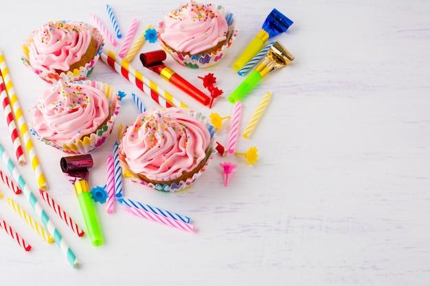 Fondo de cumpleaños con cupcakes rosas y velas de cumpleaños