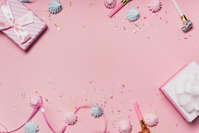 Fondo de fiesta rosa con dulces; sopladores de fiesta y cinta de rizo