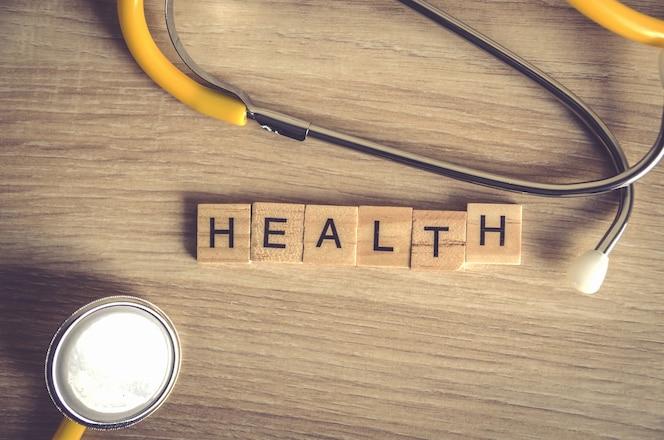 Fondo de palabra de salud en bloques de madera con stethoscop amarillo sobre fondo de madera