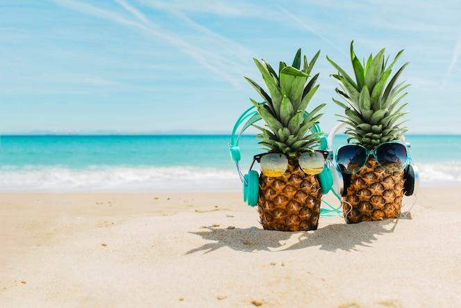 Fondo de playa con piñas chulas con auriculares
