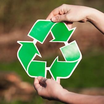 Fondo de reciclaje con mujer sujetando signo de reciclaje