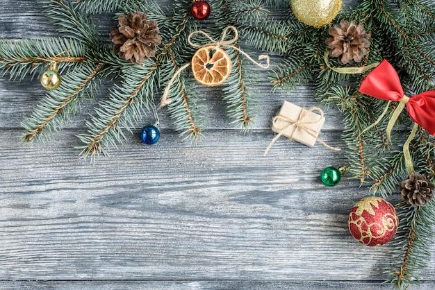 Fondo de decoración de navidad o año nuevo con ramas de abeto, conos, bolas, sobre tabla de madera gris.