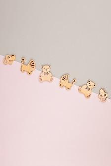 Fondo decorativo pastel mínimo con pequeñas figuras de madera para cumpleaños de recién nacidos