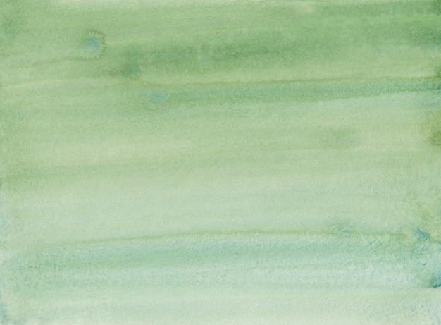 Fondo degradado de color verde césped acuarela. pintura de color verde agua ombre. trazos de pincel sobre papel.