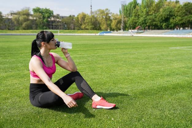 Fondo de deporte con espacio de copia. mujer deportista toma un descanso y toma agua