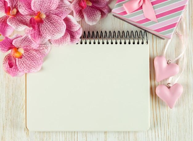 Fondo del día de san valentín con bloc de notas vacío para texto, caja de regalo, flor de orquídea rosa y corazones en la superficie de madera blanca. vista plana endecha, superior.