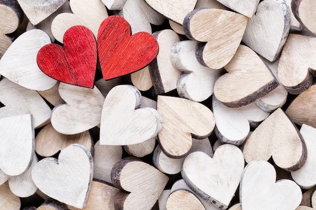 Fondo del día de san valentín con corazones rojos de extremo blanco sobre fondo de madera.