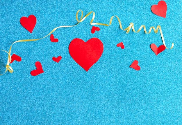 Fondo del día de san valentín con corazones rojos sobre fondo azul.