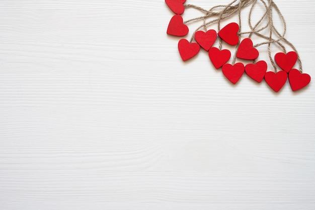 Fondo del día de san valentín. decoración roja de los corazones en el fondo blanco.