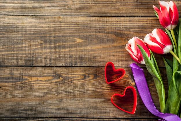 Fondo del día de san valentín para felicitaciones, tarjetas de felicitación. flores de tulipanes de primavera fresca con corazones rojos, sobre un fondo de madera vista superior copia espacio