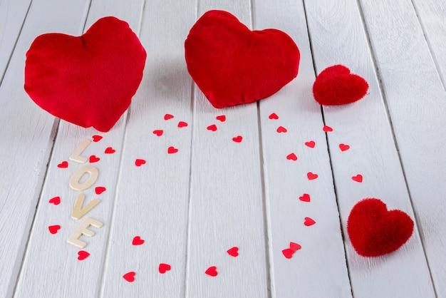 Fondo del día de san valentín con forma de corazón rojo en mesa de madera blanca