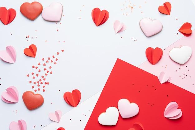Fondo del día de san valentín con galletas, corazones rojos y rosados sobre fondo pastel