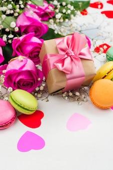 Fondo del día de san valentín con rosas, macarrones y corazones decorativos.