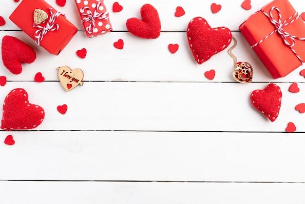 Fondo del día de tarjetas del día de san valentín, caja de regalo roja con el corazón rojo en fondo de madera.